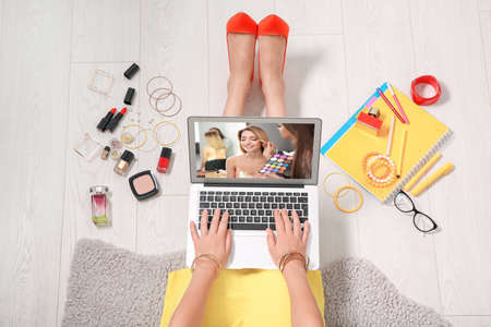 Photo for Woman sitting on floor with laptop and watching online training for professional makeup artist - Royalty Free Image