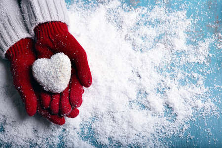 Foto de Female hands in mittens with decorative heart on snow background - Imagen libre de derechos