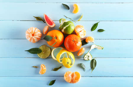 Photo pour Fresh citrus fruits with green leaves on wooden background - image libre de droit