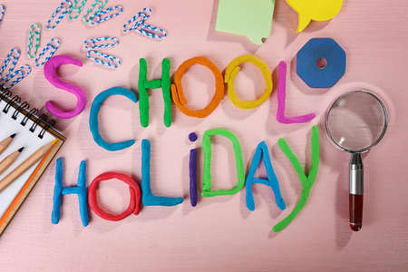 Photo pour Inscription SCHOOL HOLIDAY made of colorful plasticine and stationery on sheets of paper background - image libre de droit
