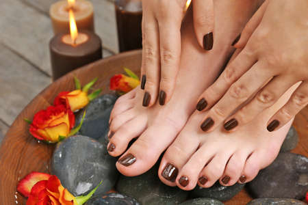 Photo pour Manicured female feet and hands in spa wooden bowl with flowers and water closeup - image libre de droit