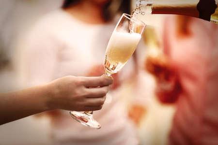 Foto de Pouring champagne into glass at hen-party, close up - Imagen libre de derechos