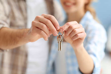 Foto de Young happy couple holding keys from their new apartment closeup - Imagen libre de derechos