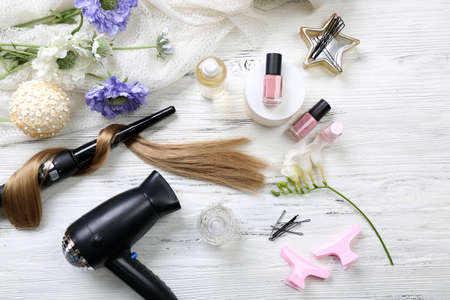 Photo for Strand of hair with flowers, barber equipment and tools on light wooden background - Royalty Free Image