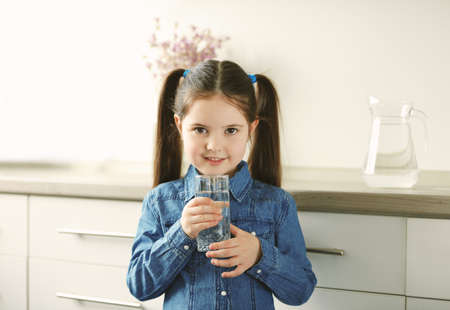 Photo for Little girl holding glass of water in living room - Royalty Free Image