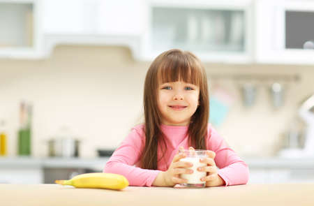 Photo for Beautiful little girl having breakfast with milk and banana in kitchen - Royalty Free Image