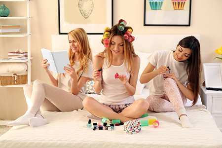 Photo pour Three girls reading book and painting fingernails on a bed in living room - image libre de droit