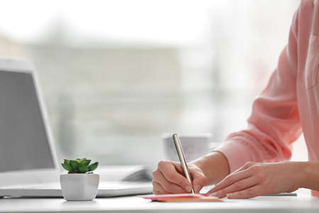 Foto de Businesswoman writing with pen in office - Imagen libre de derechos