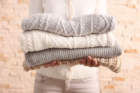 Photo pour Woman holding knitted clothes, closeup - image libre de droit