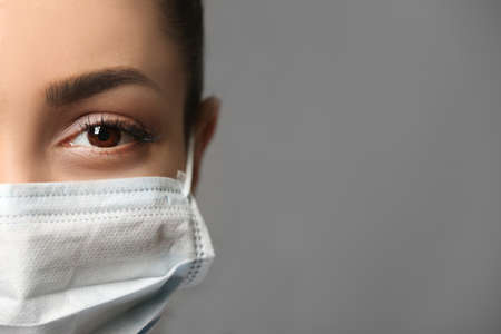 Photo pour Young female doctor in medical mask on grey background - image libre de droit