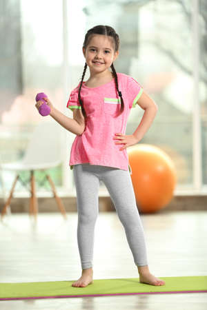 Photo for Little cute girl doing exercises with dumbbells on a mat indoor - Royalty Free Image