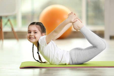 Photo for Little cute girl practicing yoga pose on a mat indoor - Royalty Free Image