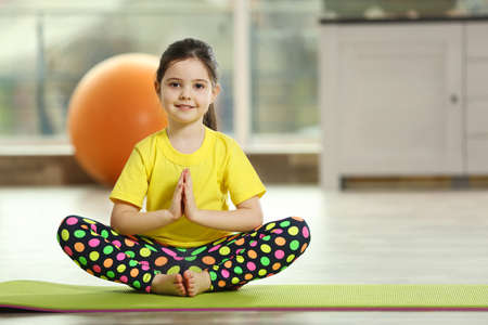 Foto de Little cute girl practicing yoga pose on a mat indoor - Imagen libre de derechos
