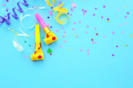 Photo for Blowers, streamers and confetti on blue background - Royalty Free Image