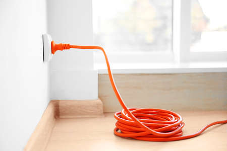 Foto de Orange extension into power outlet indoors - Imagen libre de derechos