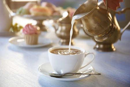 Foto de Pouring milk into cup of tea on wooden table closeup - Imagen libre de derechos