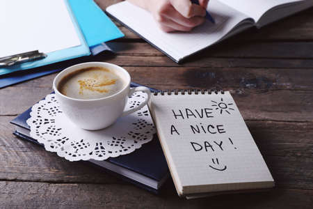 Photo for Female hands writing in notebook near cup of coffee and note HAVE A NICE DAY on wooden table closeup - Royalty Free Image