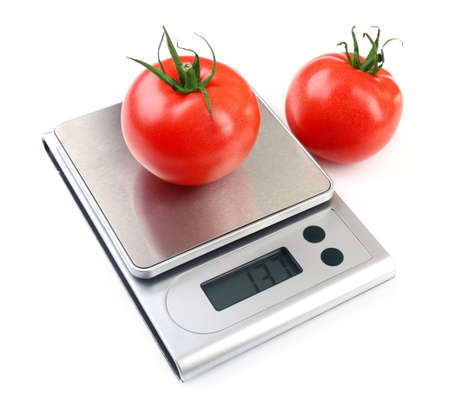 Foto de Two tomatoes with digital kitchen scales, isolated on white - Imagen libre de derechos