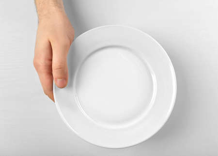 Photo pour Male hand holding white plate, isolated on white - image libre de droit