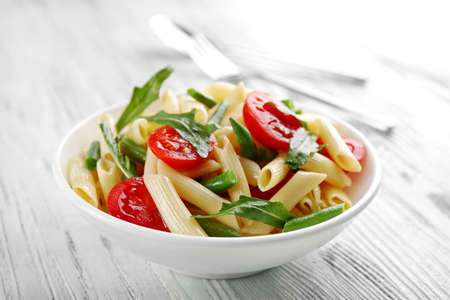 Photo pour Boiled penne pasta with tomatoes, French bean and arugula on white plate - image libre de droit