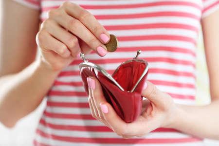 Foto de Young woman getting euro coin from purse - Imagen libre de derechos