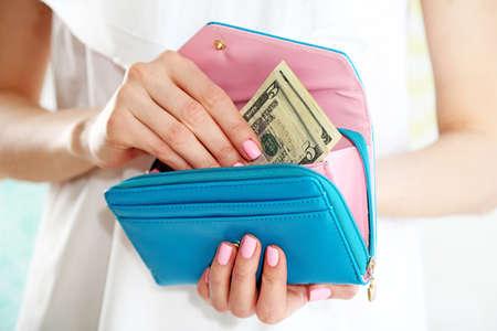 Foto de Young woman getting dollars banknotes from purse - Imagen libre de derechos