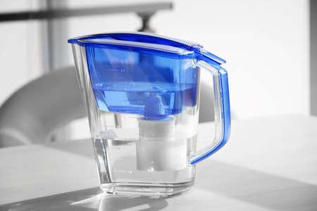Foto de Water filter jug on light wooden table - Imagen libre de derechos