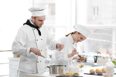 Foto de Male and female chefs working at kitchen - Imagen libre de derechos