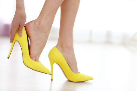 Foto de Woman taking off yellow high heels shoes. - Imagen libre de derechos