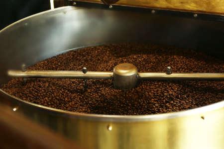 Foto de Freshly roasted coffee beans in a coffee roaster - Imagen libre de derechos