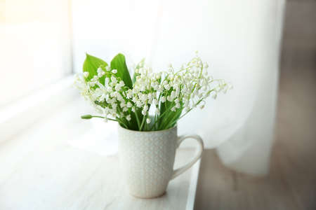 Photo pour Bouquet of lilies of the valley on windowsill - image libre de droit