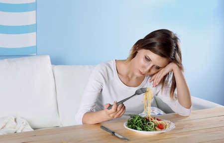 Foto de Young depressed girl with eating disorder at wooden table - Imagen libre de derechos