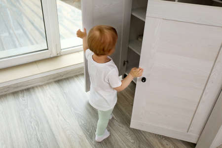 Photo for Cute baby girl playing with a wooden cupboard - Royalty Free Image