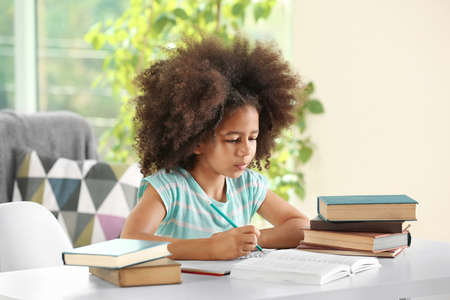 Photo pour Cute African girl doing homework - image libre de droit