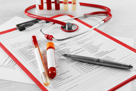 Photo pour Blood samples and stethoscope on medical report - image libre de droit