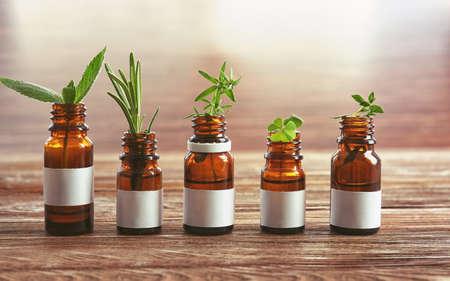 Foto de Dropper bottles and herbs on wooden table - Imagen libre de derechos