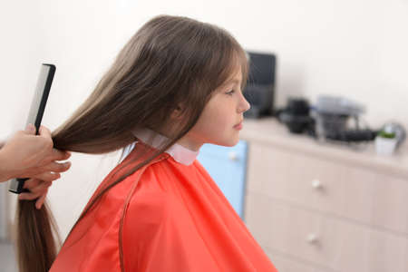 Photo pour Small girl in hairdressing salon - image libre de droit
