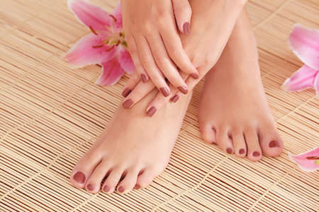 Photo pour Female feet and hands with brown manicure on bamboo mat background - image libre de droit