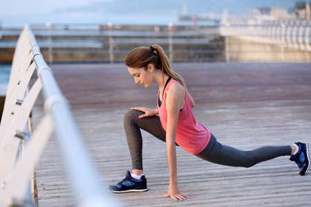 Photo pour Young woman doing exercises on pier - image libre de droit