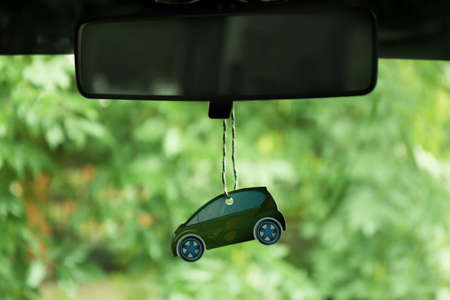 Photo for Air freshener hanging in the car on green natural background - Royalty Free Image