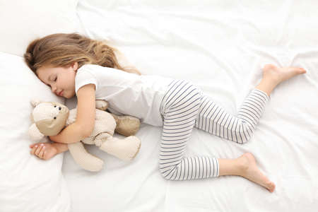 Photo pour Cute little girl sleeping with teddy bear in bed - image libre de droit