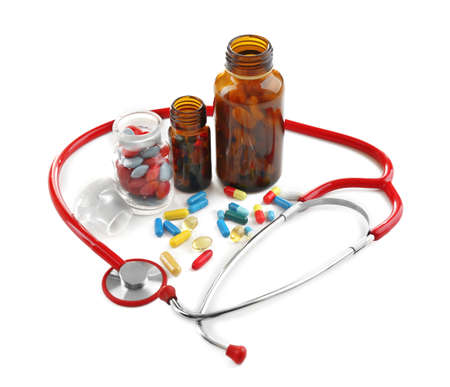 Foto de Stethoscope with colorful pills isolated on white background - Imagen libre de derechos