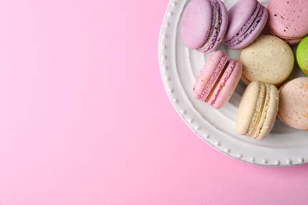 Photo pour Tasty colorful macaroons in white plate on pink background - image libre de droit