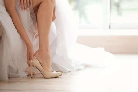 Photo pour Bride in a beautiful wedding dress putting on shoes - image libre de droit