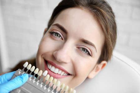 Foto de Young woman choosing color of teeth at dentist - Imagen libre de derechos