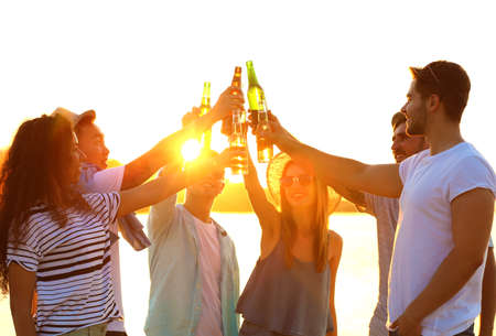 Photo pour Group of friends hanging out with beer at the beach - image libre de droit