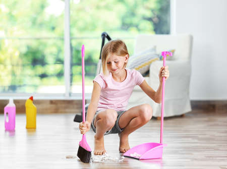 Photo pour Little girl sweeping floor - image libre de droit