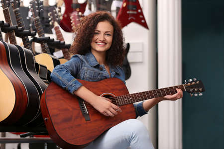 Photo for Beautiful girl playing guitar in music shop - Royalty Free Image