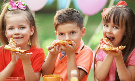 Photo for Children eating pizza in park - Royalty Free Image