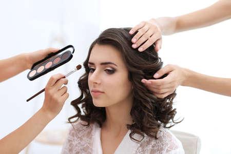 Photo pour Makeup artist and hairdresser preparing bride before her wedding - image libre de droit